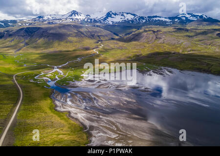 The road winding around Snaefellsness Peninsula with a braided river running into the ocean; Iceland - Stock Photo