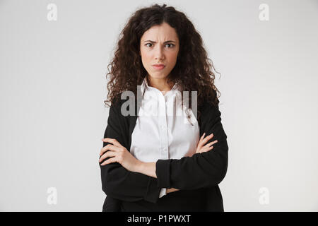 Portrait of an upset young businesswoman standing with arms folded and looking at camera isolated over white background - Stock Photo