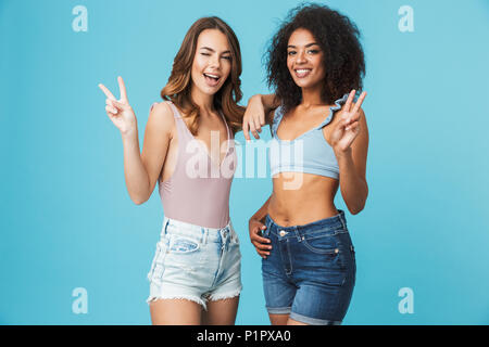 Two cheerful young girls dressed in summer clothes showing peace gesture isolated over blue background - Stock Photo