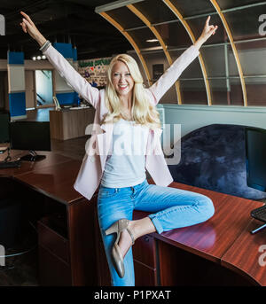 Beautiful young millennial business woman with long blond hair celebrating success and posing for the camera in the workplace - Stock Photo