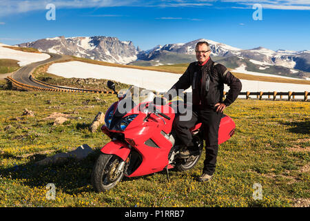 View from the Beartooth Highway of the Beartooth Mountains and a man posing with a motorcycle parked on the roadside - Stock Photo