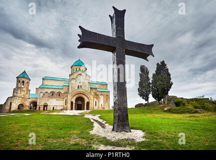 Big iron Cross in front of Bagrati church at overcast sky in Kutaisi, Georgia - Stock Photo