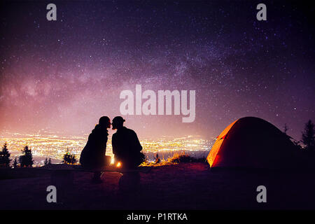 Happy couple in silhouette kissing near campfire and orange tent. Night sky with Milky Way stars and city lights at background. - Stock Photo