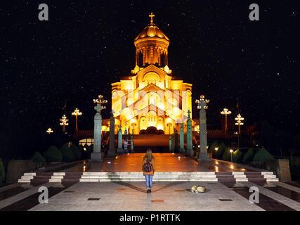 Woman near The Holy Trinity Cathedral or Tsminda Sameba Church at night in Tbilisi, Georgia - Stock Photo