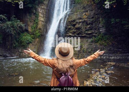 Woman in Hat rise her hand near waterfall in Botanical Garden in Tbilisi, Georgia - Stock Photo