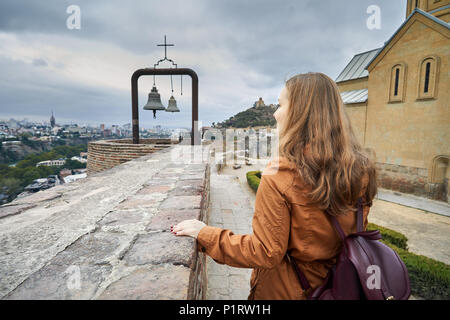 Tourist woman near Bells at Cathedral in Old medieval castle Narikala at overcast cloudy sky in Tbilisi, Georgia - Stock Photo
