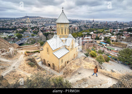 Tourist woman walking near Cathedral in Old medieval castle Narikala at overcast cloudy sky in Tbilisi, Georgia - Stock Photo