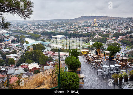 Empty cafe at Narikala Fortress with panoramic view Tbilisi at overcast sky, Georgia - Stock Photo