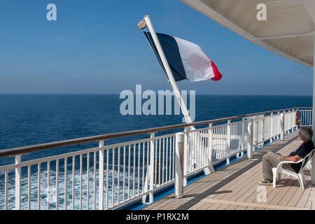 French Fag blowing in the wind on board a ferry from Roscoff to Plymouth - Stock Photo