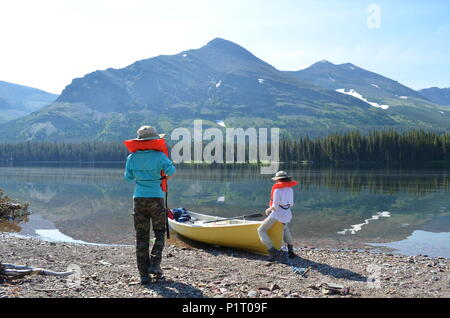 Two girls boating on Lake Waterton in Alberta, Canada. - Stock Photo