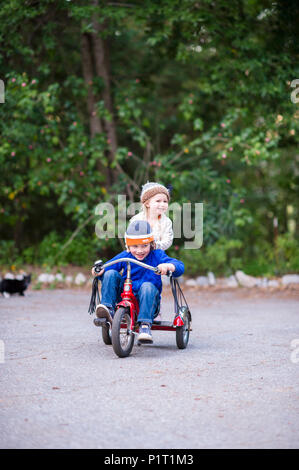 Young brother and sister riding on a tricycle and laughing in a garden setting. - Stock Photo
