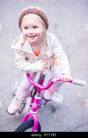 Young girl in stylish clothing on her pink bicycle - Stock Photo