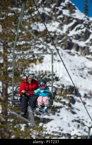 Mother and young daughter on a ski lift at Squaw Valley Ski Resort in California, North America. - Stock Photo
