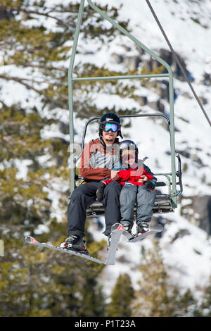 Father and son on a ski lift at Squaw Valley Ski Resort in California, North America. - Stock Photo