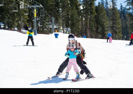 Father teaching daughter how to ski at Squaw Valley Ski Resort in California, North America. - Stock Photo