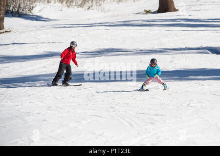Mother teaching young daughter how to ski at Squaw Valley Ski Resort in California, North America. - Stock Photo