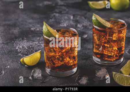 Rum and cola cuba libre with lime and ice, selective focus. - Stock Photo