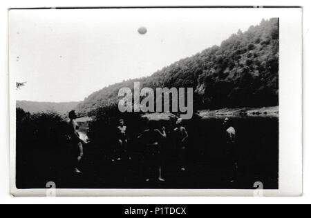 THE CZECHOSLOVAK SOCIALIST REPUBLIC - CIRCA 1950s: Retro photo shows people on the vacation. Young people play with ball. Summer holiday theme. Vintage black & white photography. - Stock Photo