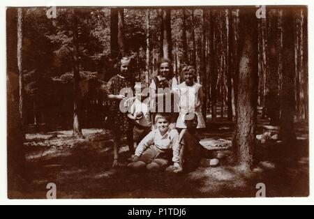 THE CZECHOSLOVAK REPUBLIC - JULY, 1925: Vintage photo shows children in the forest. Retro black & white photography. - Stock Photo