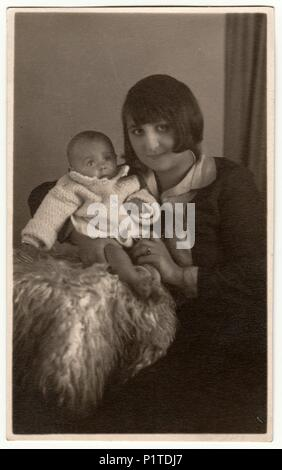 THE CZECHOSLOVAK REPUBLIC - CIRCA 1930s: Vintage photo shows woman with baby (newborn). Retro black & white studio photography. - Stock Photo