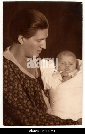 THE CZECHOSLOVAK REPUBLIC - CIRCA 1930s: Vintage photo shows woman with baby (newborn) in swaddling clothes. Retro black & white studio photography. - Stock Photo