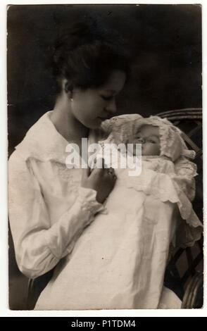 GERMANY - APRIL 25, 1918: Vintage photo shows woman with baby (newborn) in swaddling clothes. Retro black & white studio photography. - Stock Photo