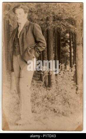 THE CZECHOSLOVAK REPUBLIC - CIRCA 1930s: Vintage photo shows a young man in the forest. Retro black & white photography. With original film grain, blur and scratches. - Stock Photo