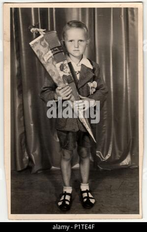 GERMANY - CIRCA 1940s: Vintage photo shows pupil boy with 'Schultute' or School Cone, sweets for the first day in school. Studio photo with sepia tint. - Stock Photo