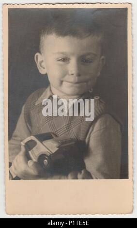 MAGDEBURG, GERMANY - CIRCA 1940s: Vintage photo shows boy holds toy car.  Black & white photography - Stock Photo