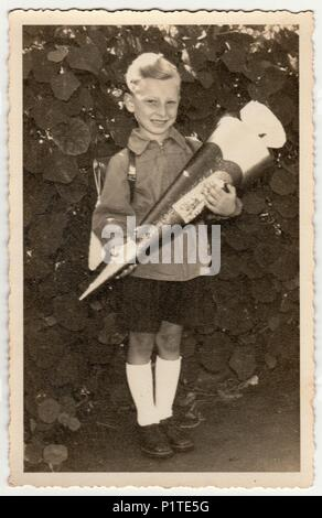 GERMANY- CIRCA 1940s: Vintage photo shows pupil boy with 'Schultute' or School Cone, sweets for the first day in school. Studio photo with sepia tint. - Stock Photo