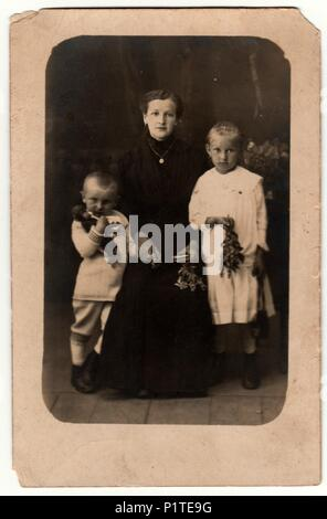 GERMANY - CIRCA 1930s: Vintage photo shows woman and her children in a photography studio. Boy wears a sailor costume and girl white dress. Retro black & white studio photography with sepia effect. - Stock Photo