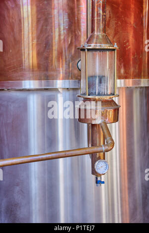 Alcohol copper still alembic with control gauge closeup inside distillery - Stock Photo