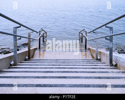 concrete stairs or steps leading down into ocean water - Stock Photo