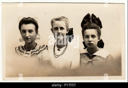 HAMBURG, GERMANY - CIRCA 1940s: Vintage photo shows a group of girls poses in the photography studio. Girls wears hair ribbon and some of them necklace ((string of) beads ). Retro black & white photography with sepia effect. - Stock Photo