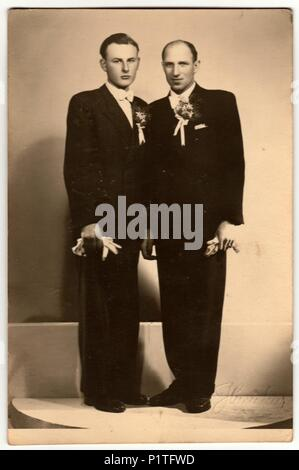 ZLIN, THE CZECHOSLOVAK REPUBLIC - CIRCA 1920s: Vintage photo shows two men (groom and his best man) pose in photography studio. Retro black & white photography. - Stock Photo