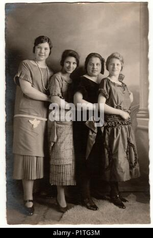 HAMBURG, GERMANY - CIRCA 1930s: Vintage photo shows a group of girls poses in the photography studio. Retro black & white photography with sepia effect. - Stock Photo