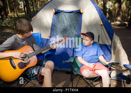 A teenage boy playing guitar on a camping trip. - Stock Photo