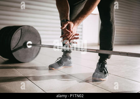 Close-up of a strong man's hands getting ready to weightlifting at the garage gym. - Stock Photo