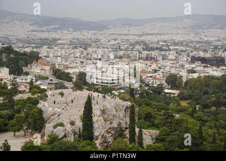 Athens, Greece - April 16, 2018: View from the Acropolis of the Athens skyline and the Areopagus (Ares Rock), under a hazy sky caused by dust clouds. - Stock Photo