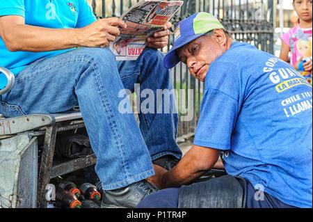 Man shining shoes in downtown Guayaquil, Ecuador - Stock Photo