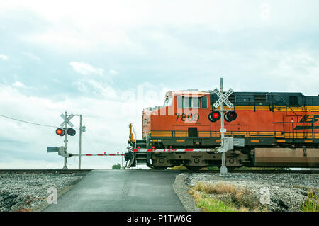 Train engine crossing a road with the crossing gates down and lights flashing. - Stock Photo
