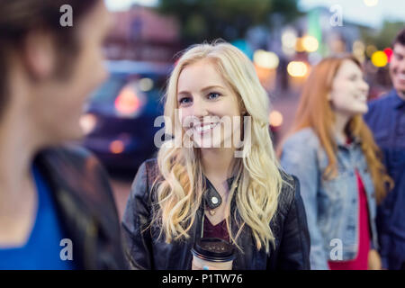 Two young couples walk down a popular street at dusk, focus is on a young woman with blond hair; Edmonton, Alberta, Canada