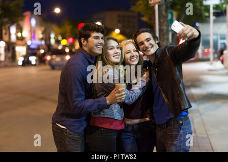 Two young couples stand closely together on the street at nighttime to pose for a self-portrait with a smart phone; Edmonton, Alberta, Canada - Stock Photo