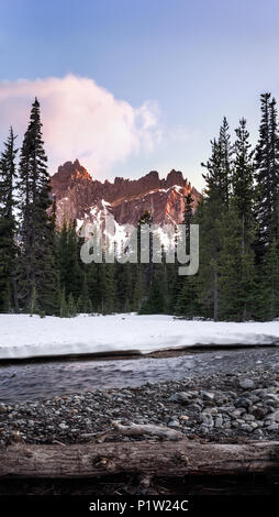 Forest scene of mountain illuminated by sunset with snow, trees and river in foreground - Stock Photo