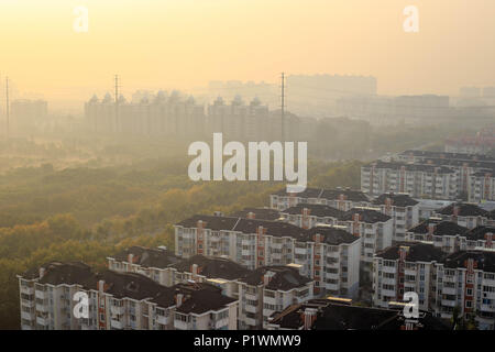 Smog combines with early morning mist as sun rises over apartment blocks in a Shanghai suburb - Stock Photo