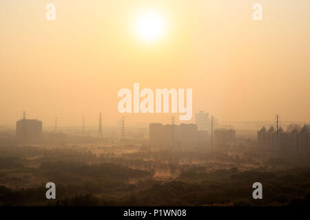 Bright sun rising over power lines and morning haze in a Shanghai suburb - Stock Photo