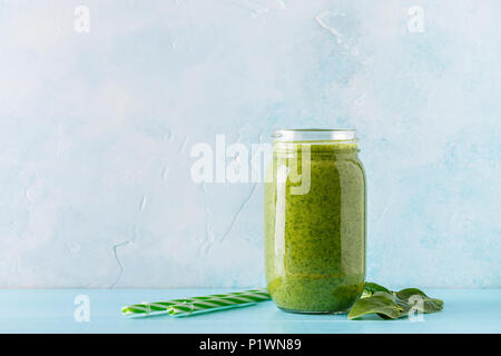 Green-colored smoothies / juice in a jar on a blue background. - Stock Photo