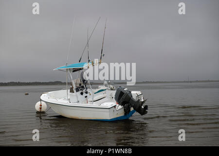 A speed boat is beached by low tide on a stormy, cloudy afternoon - Stock Photo