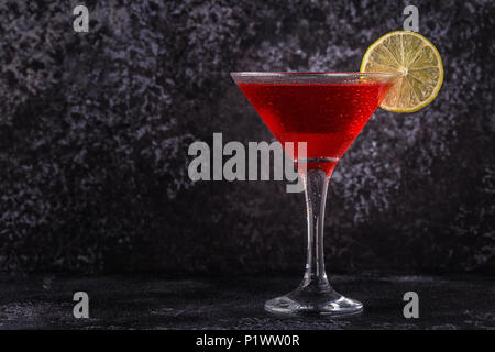 Glass of cosmopolitan cocktail decorated with lime, selective focus - Stock Photo