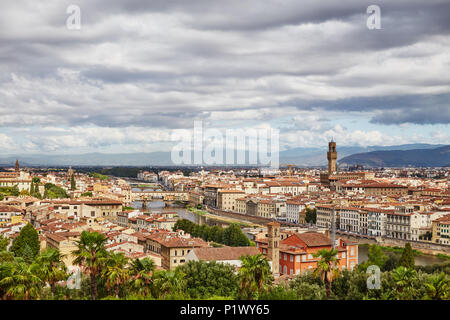 Picturesque view of Florence city with colorful old buildings under dark clouds, Italy - Stock Photo